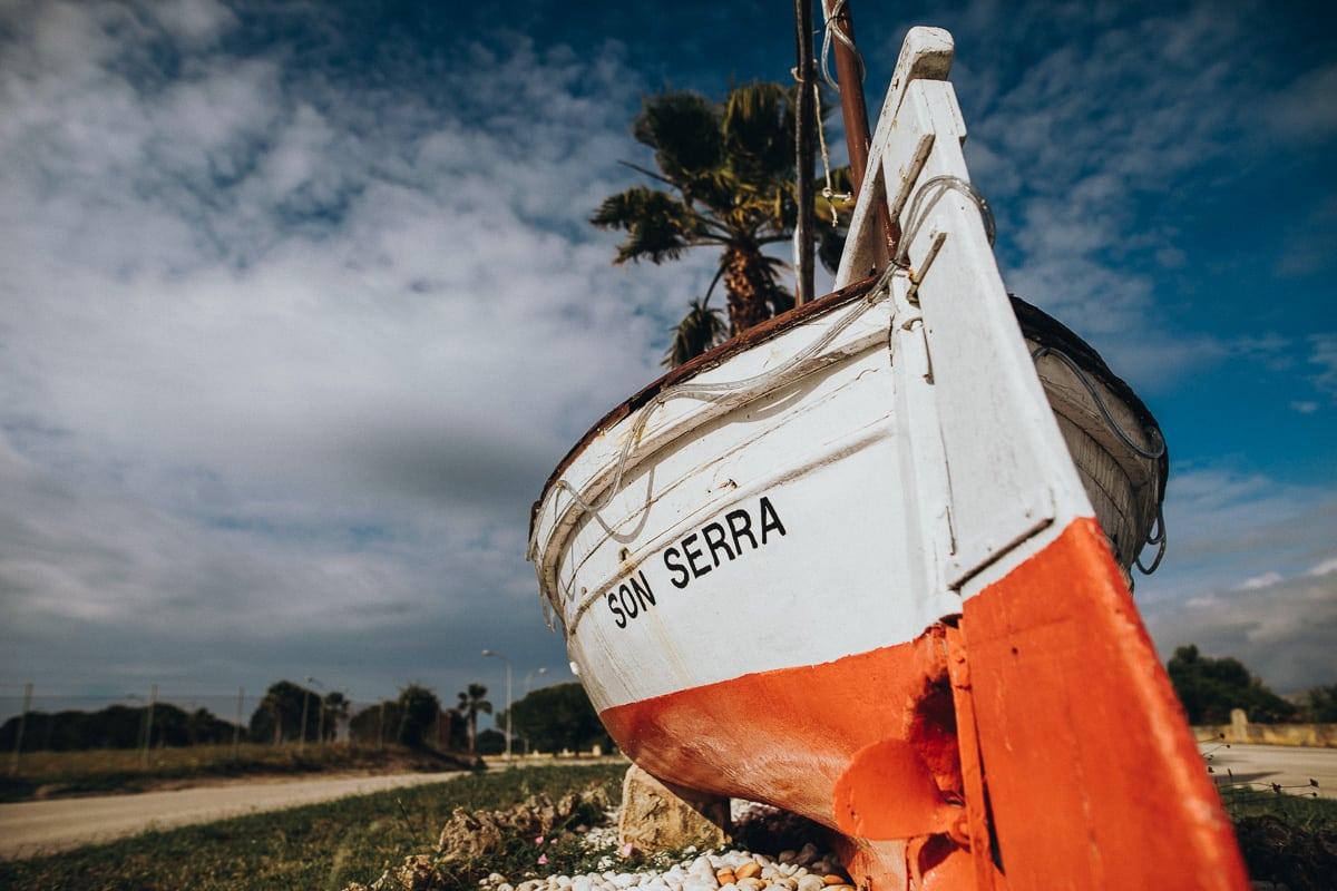Altes Boot mit der Beschrifting Son Serra als Eingangschild des mallorquinischen Fischerdorfes.