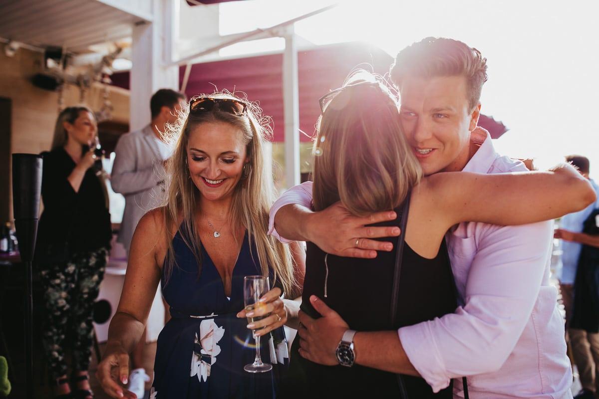 Der Bräutigam umarmt die ankommenden Gäste zur Get Together Party auf Mallorca.