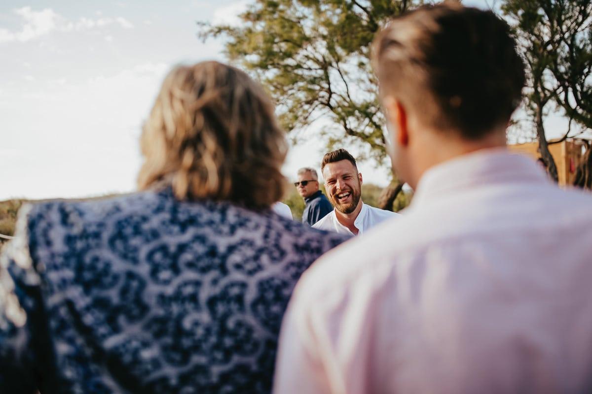Ein Hochzeitsgast lacht den Bräutigam aus ganzem Herzen an.