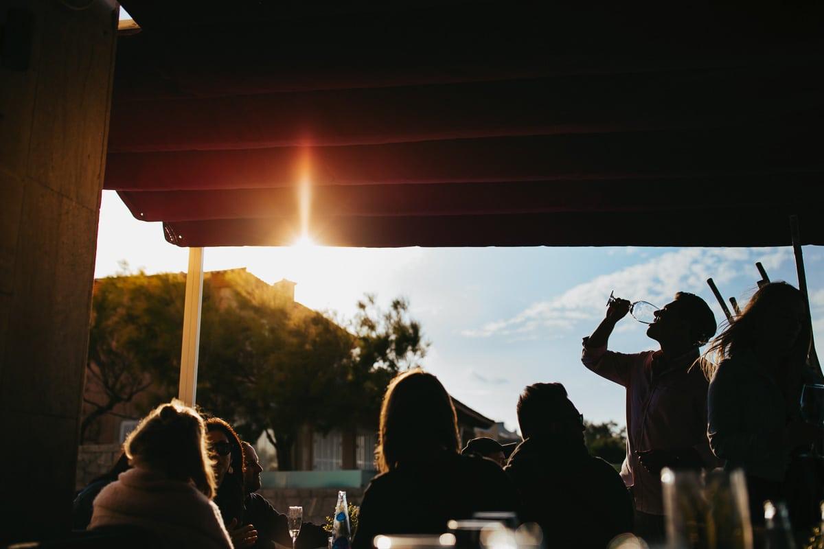 Silhouettenbild des trinkenden Bräutigams umringt von seinen Gästen.