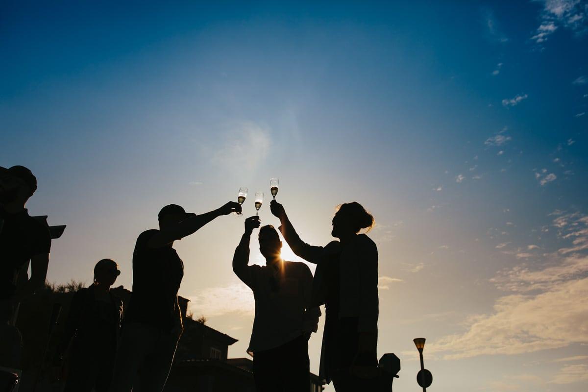 Silhouettenbild von drei Gästen welche mit einem Glas Sekt anstossen.