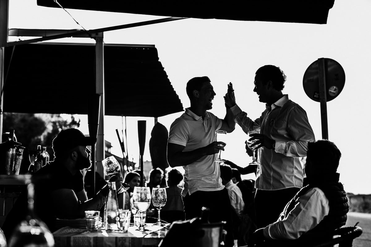 Der Bruder des Bräutigams und ein Gast geben sich herzhaft lachend high five.