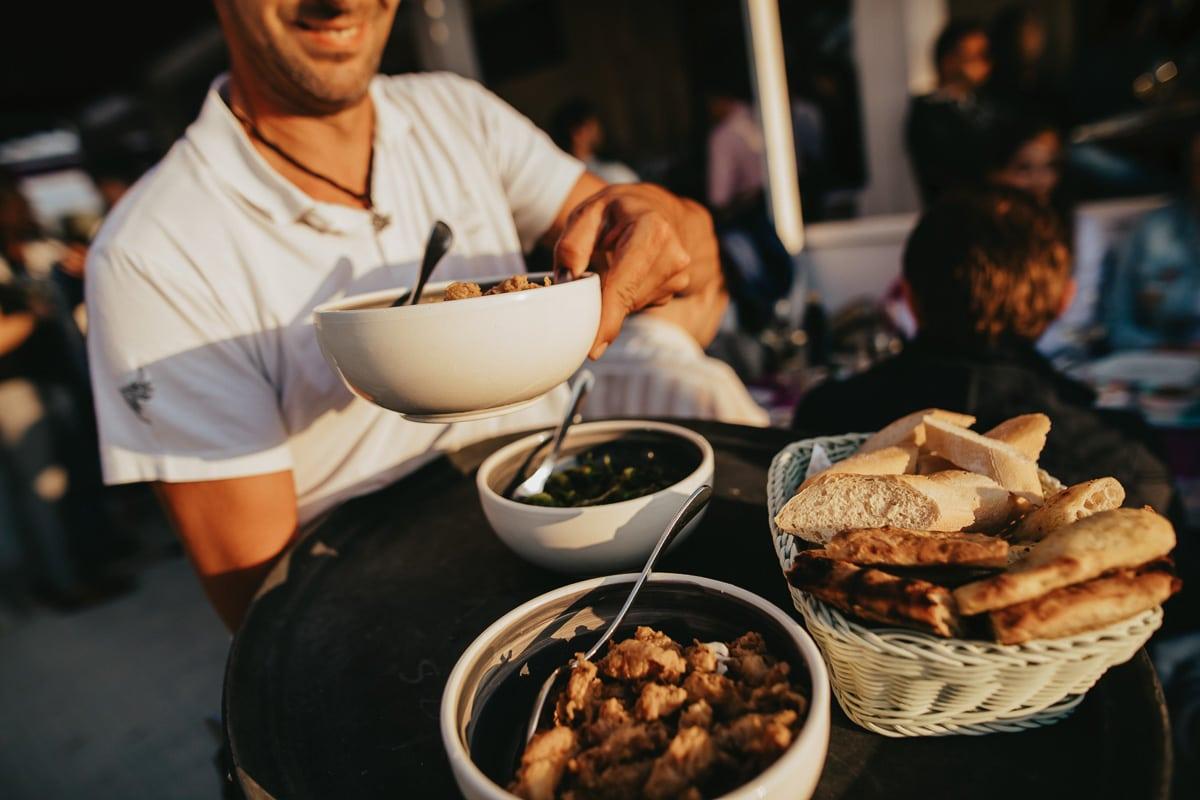 Der kellner serviert das lifestyle Abendessen iauf der Terasse der Bar Sol.