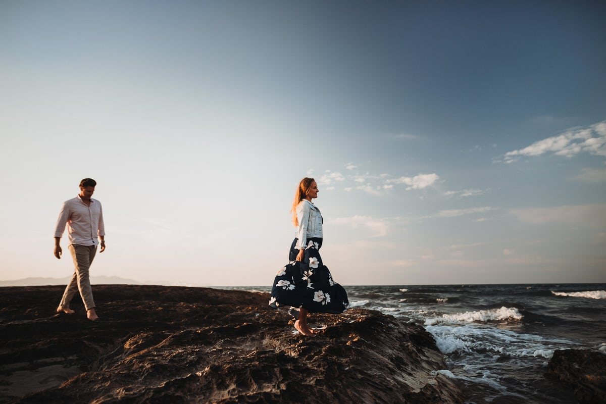 Die Braut steht auf braunen Felsen, schaut auf das Meer hinaus und ihr Bräutigam geht auf sie zu.