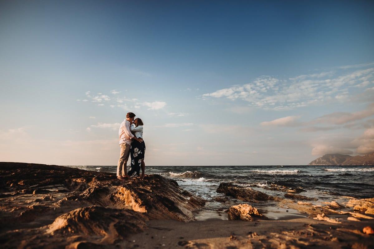 Das Brautpaar küsst sich liebevoll am Meer.