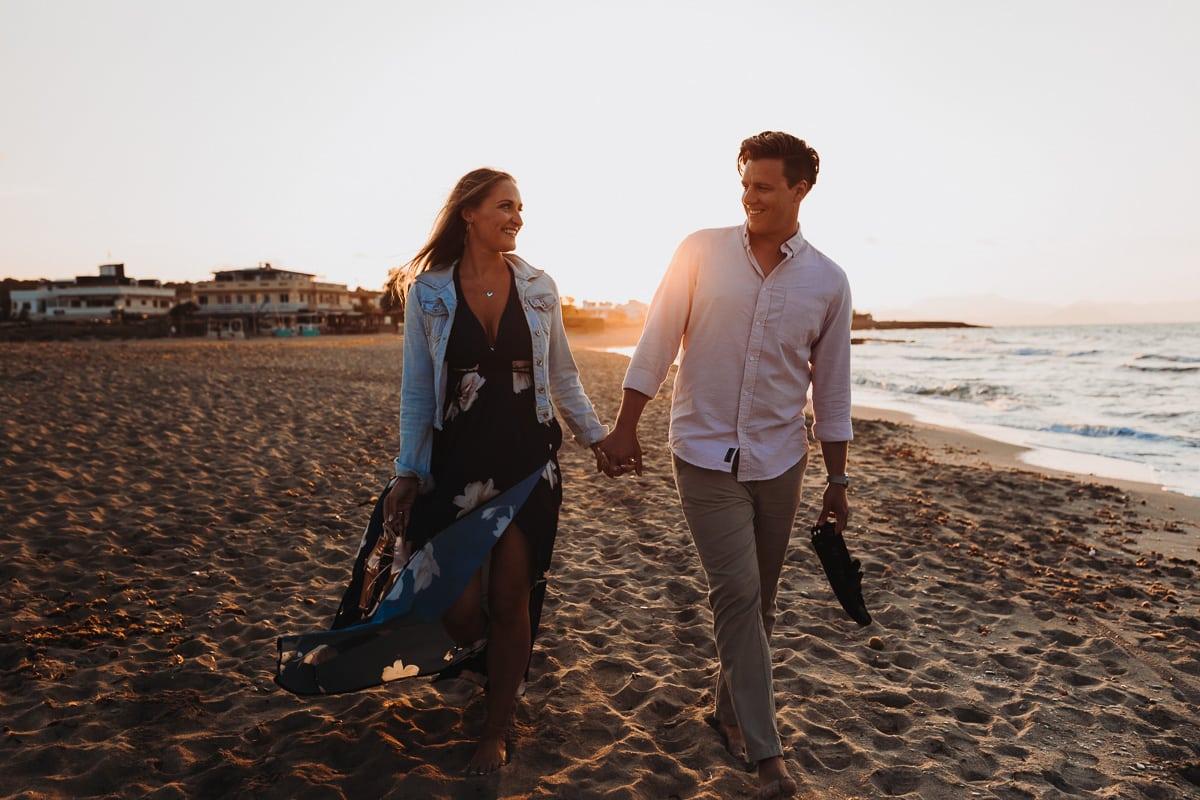 Das Brautpaar lächelt sich überglücklich an während seines Strandspaziergangs. Wir sehen die beiden von vorn.