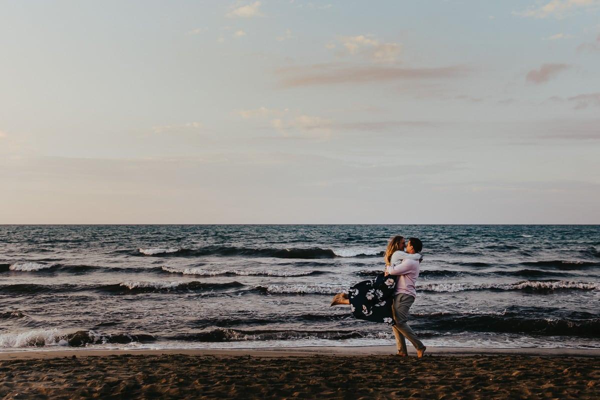 Wir sehen ein überglückliches Brautpaar vor dem Meer. Er hebt sie hoch und dreht sich.