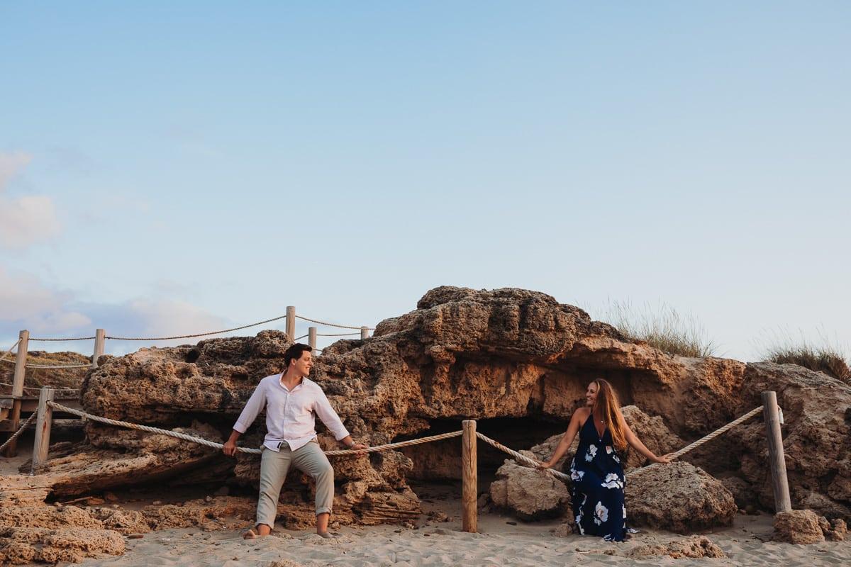 Beide sitzen auf rustikalen Seeseilen der Absperrung am Strand und lächeln sich an.