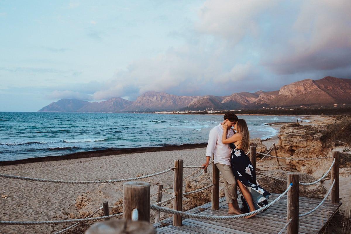 Das Brautpaar kuschelt auf dem Holzsteg der vom Strand in die Dünen führt. Wir sehen Mallorcas wundervoll blaues Meer und die Berge im Abendlicht im Hintergrund.