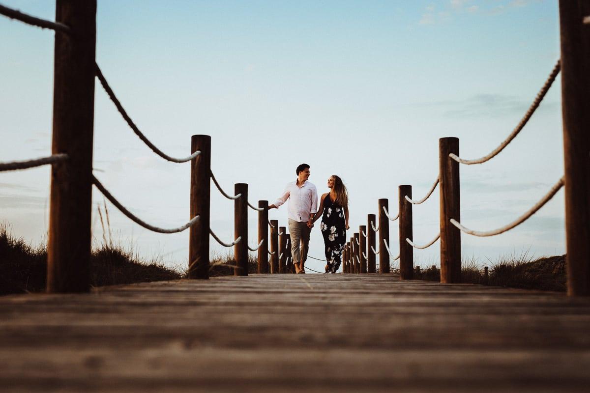 Das Brautpaar rennt Hand in Hand entzückt über den Holzsteg der in die Dünen geht.