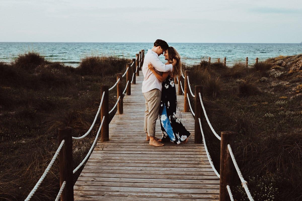 Beide halten mitten auf dem Holzsteg inne und schauen sich verliebt an. Wir sehen das Meer im Hintergrund.