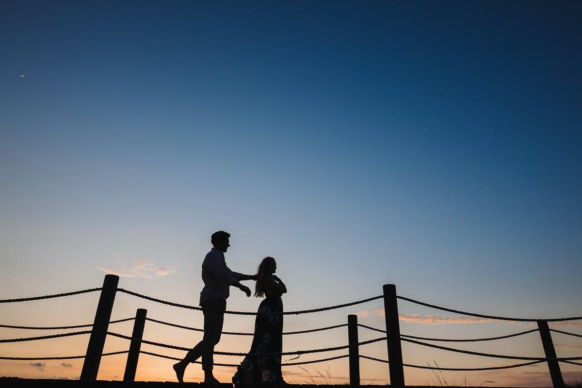 Silhouette der beiden in Sonnenuntergangsfarben wie sie auf dem Steg wieder Richtung Meer zurückgehen.