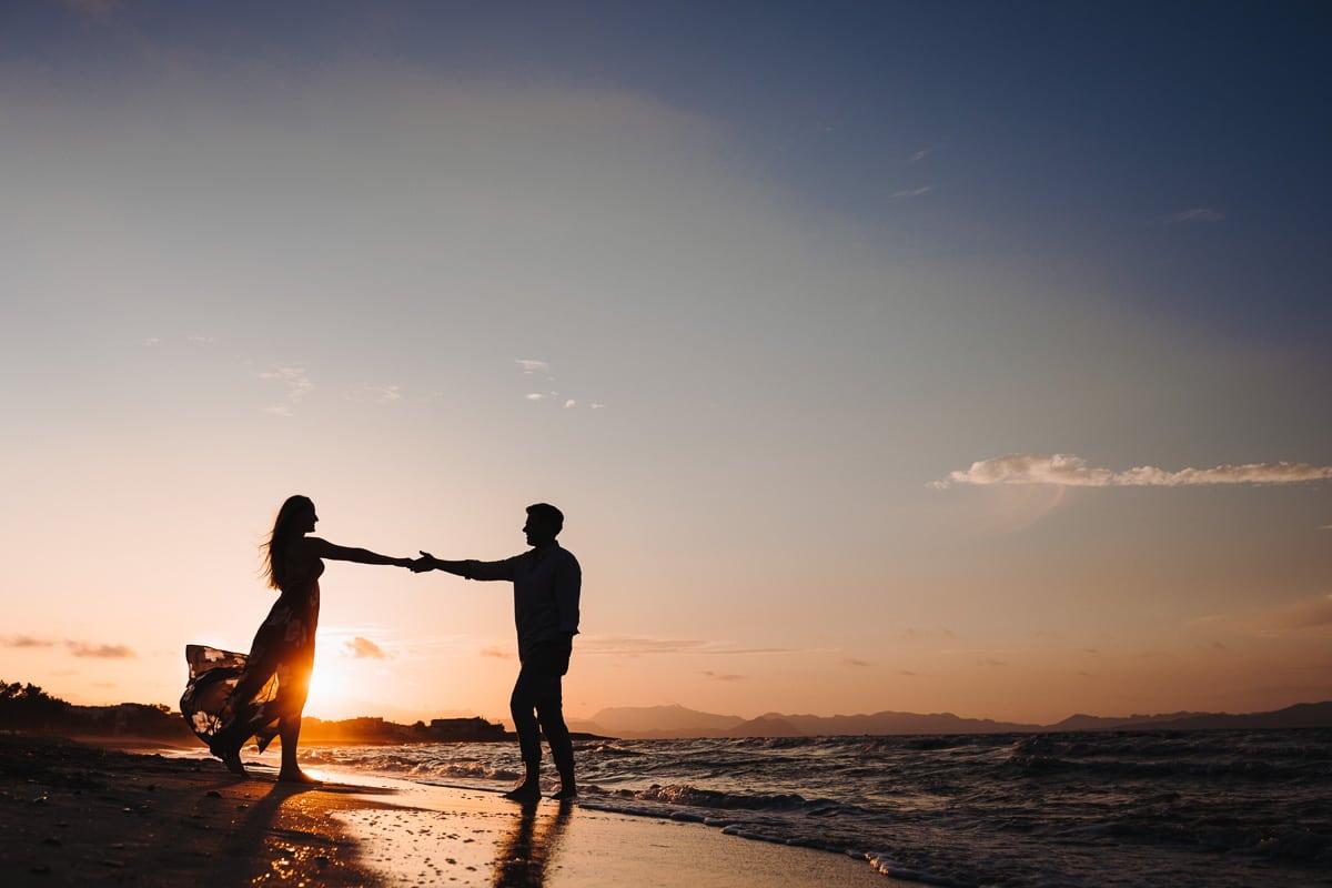 Traumhaft schönes Foto in der Abendsonne wie sie auf ihn zuläuft und er ihre Hand nimmt.