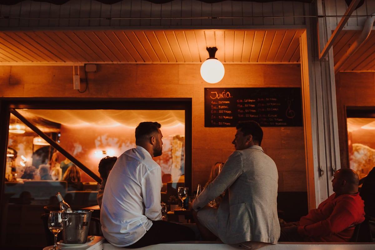 Zwei Gäste sitzen auf der Brüstung der Veranda der Bar und unterhalten sich umgeben von warmen Laternenlicht.