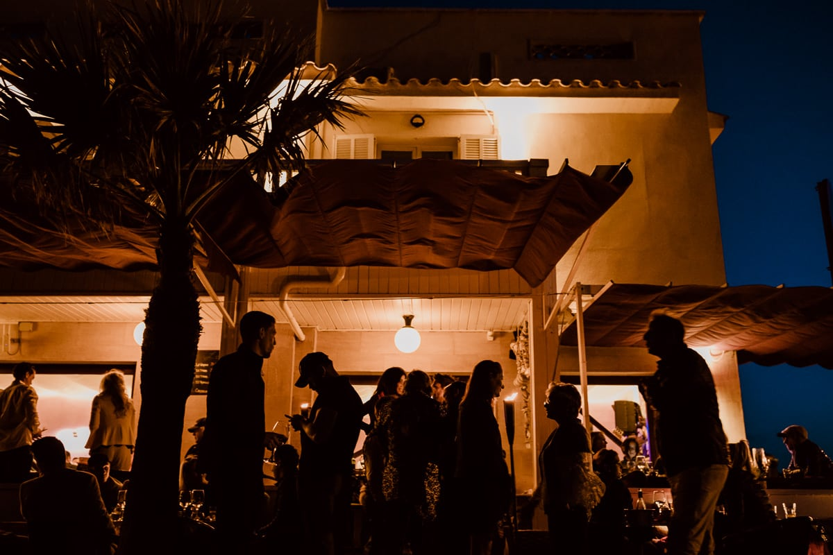 Die Bar Sol zur blauen Stunde in orangfarbener Laternenbeleuchtung mit Silhouetten der Gäste im Vordergrund.