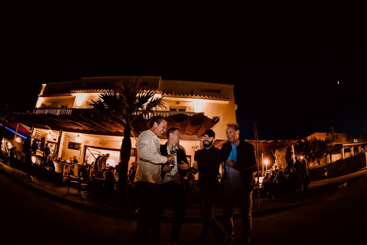 Der Bruder des Bräutigams und drei Freunde lachen herzhaft vor der angeleuchteten Bar Sol im Fischerdorf Son Serra.