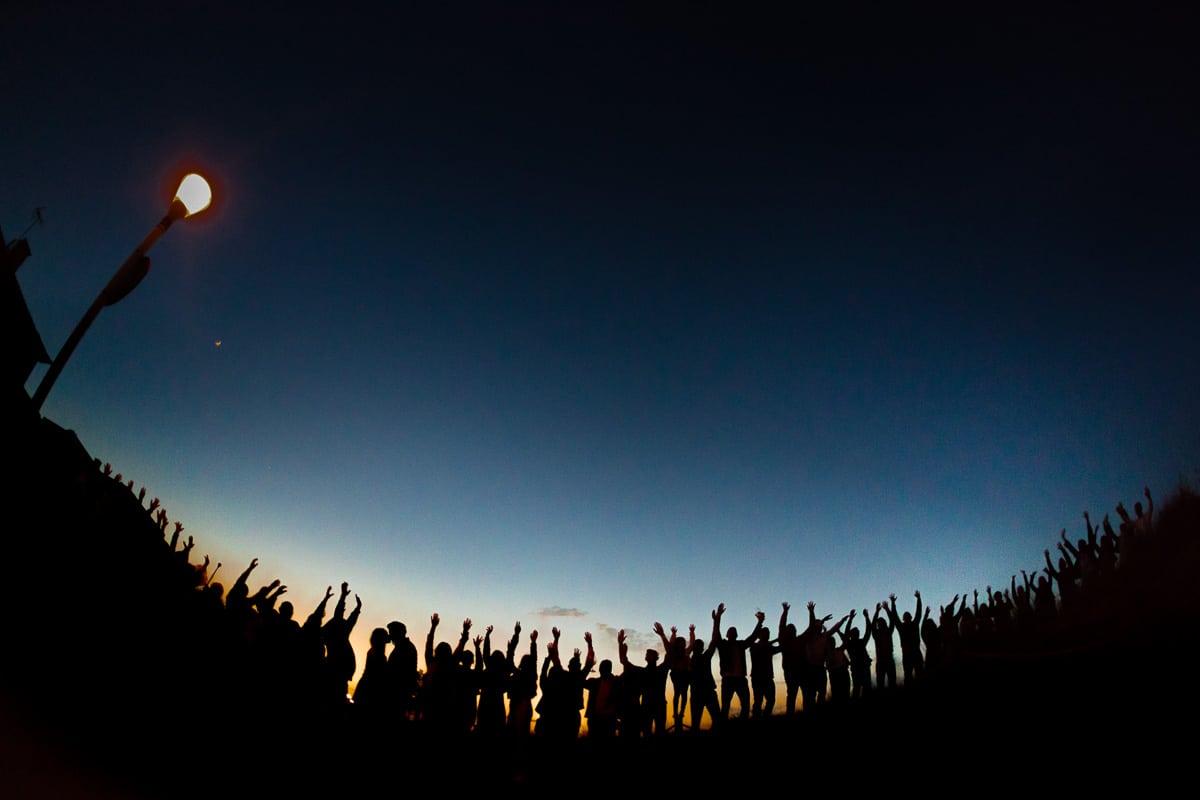 Kreatives finales Gruppenfoto mit allen armehebenden Gästen als Silhouette und dem küssenden Brautpaar vor dem blauen Abendhimmel Mallorcas.