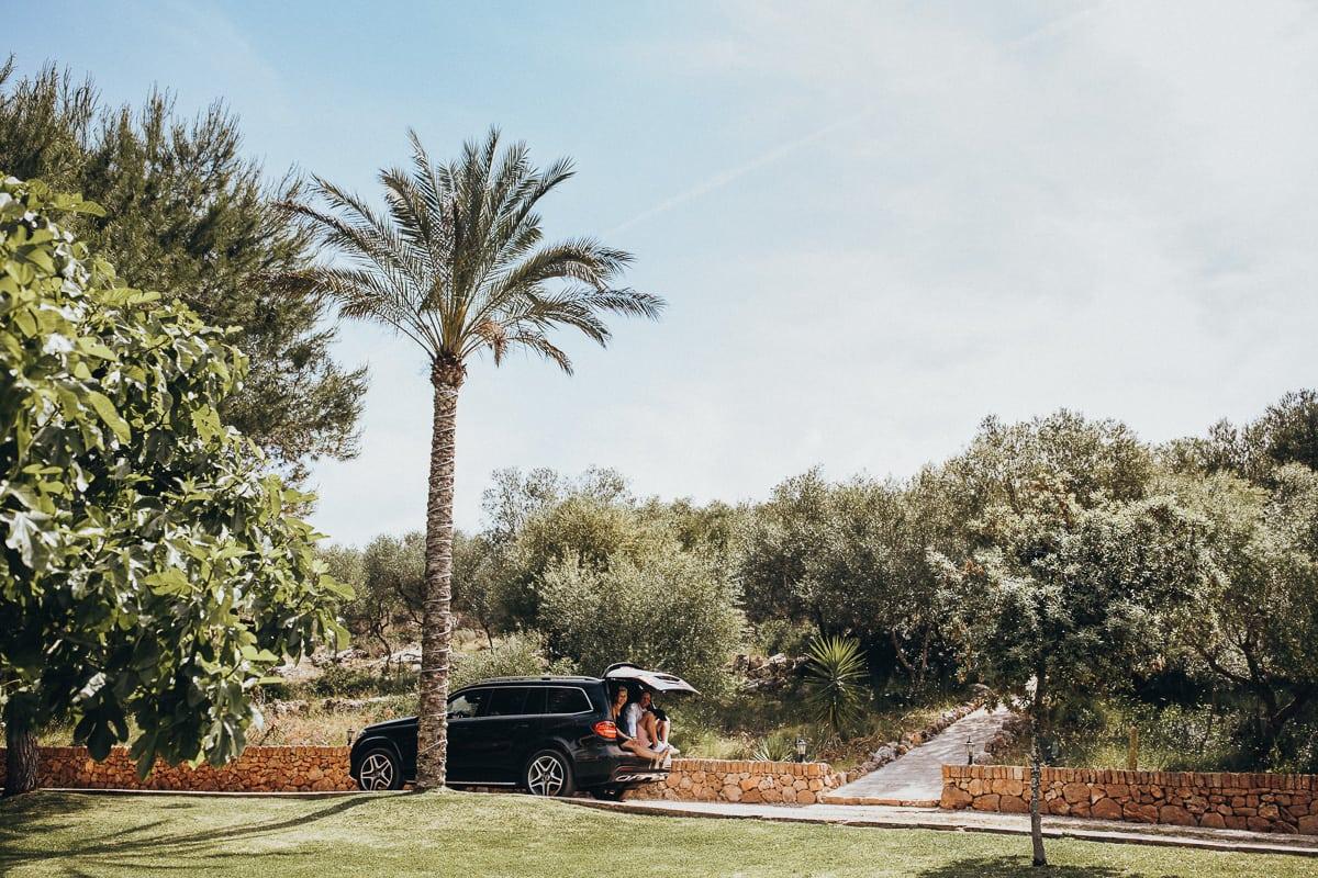 Die Freunde kommen im fahrenden Auto im offenen Kofferraum zum Hochzeitsbrunch auf der Finca Can Toni an.