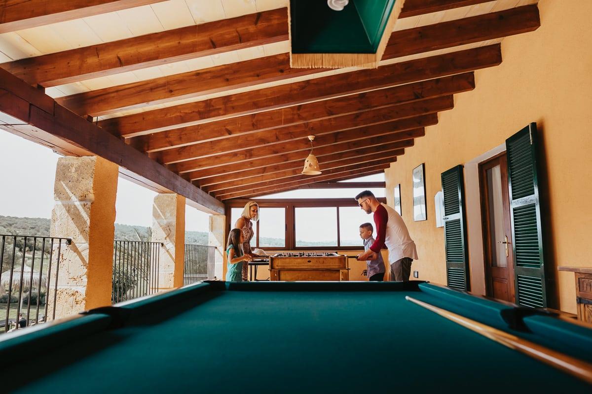 Eine Familie der Gäste spielen mit ihren zwei Kindern auf der Finca am Kickertisch.