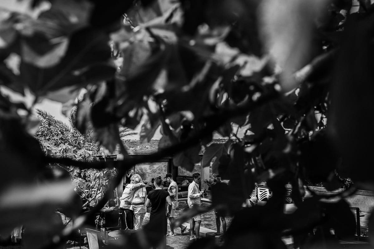Blick durch die Baumblätter auf den Vater des Bräutigams welcher von einem Freund umarmt wird.