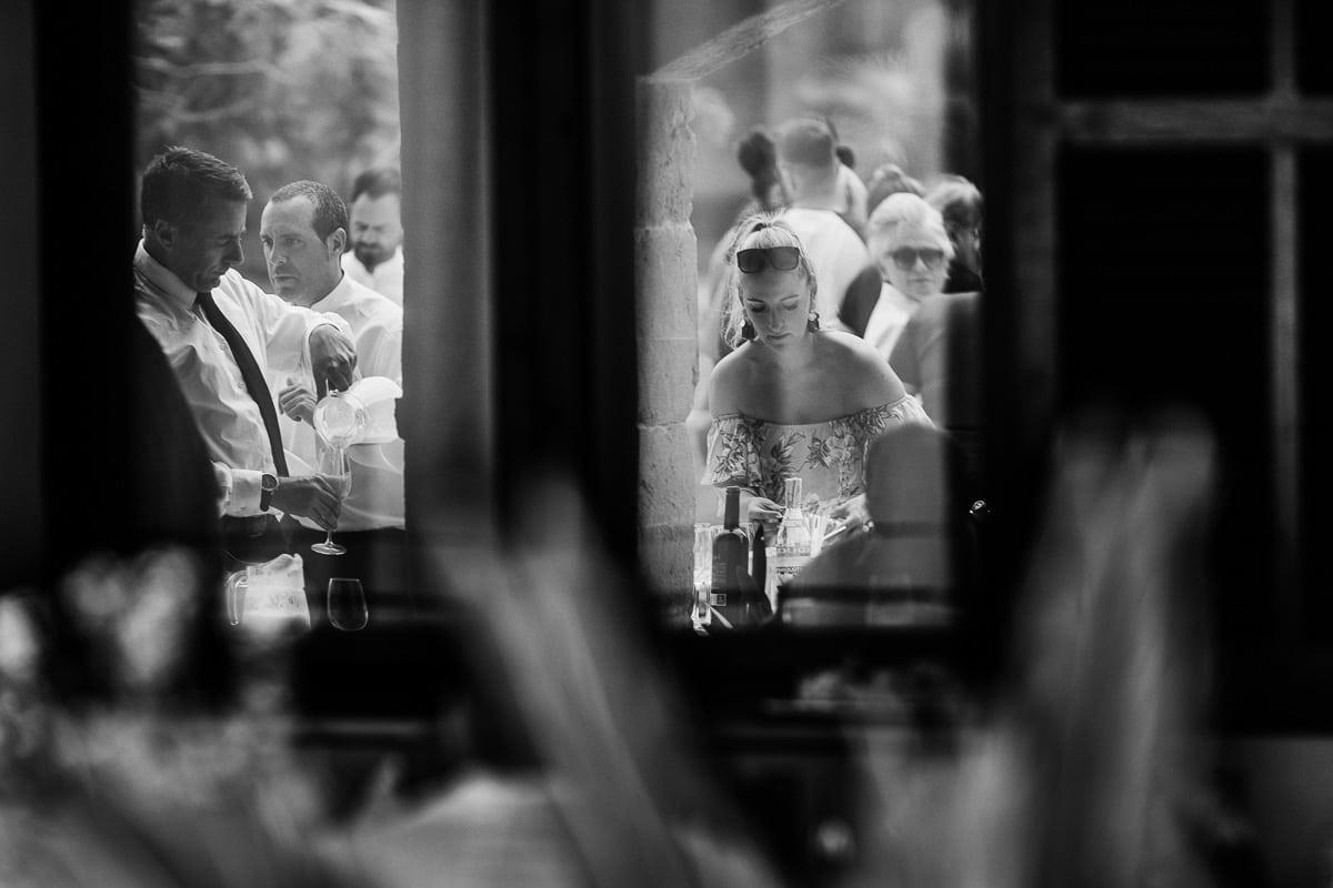 Spiegelbild der Braut im Fenster der Finca während sie sich entwas zu trinken serviert.