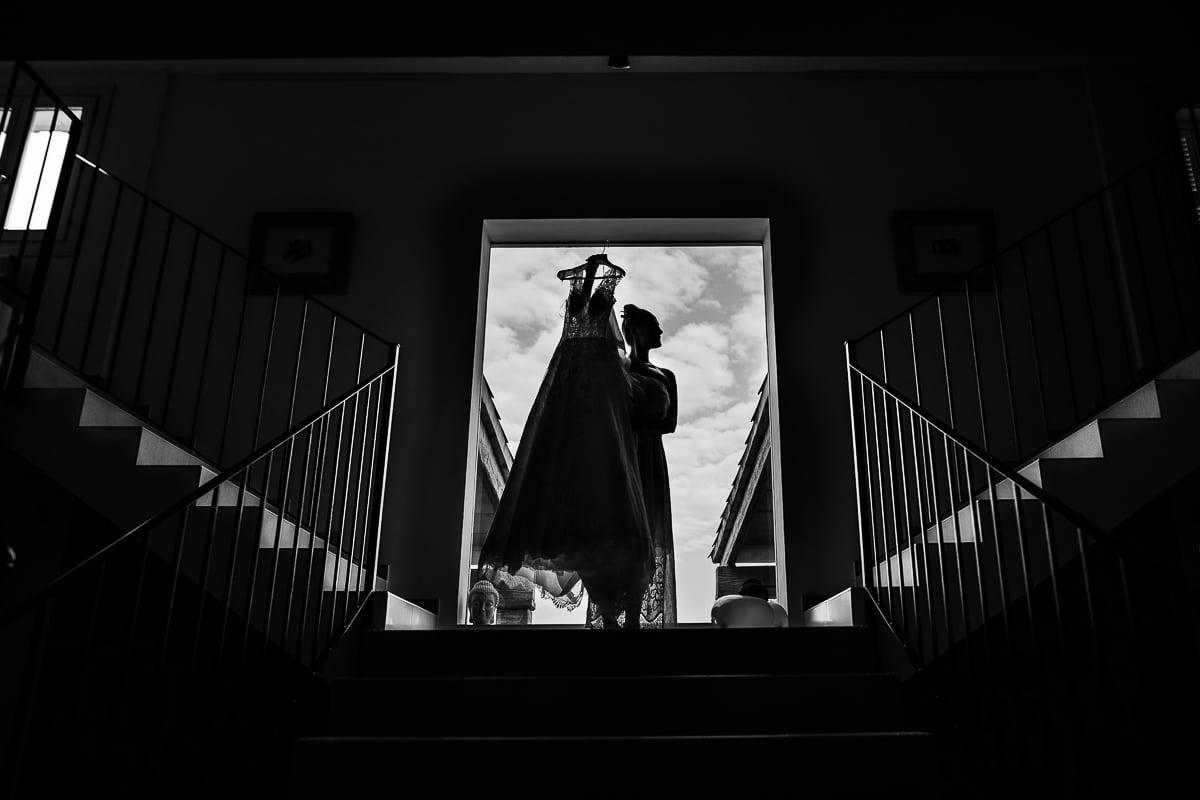 Imposantes Silhouettenfoto der Braut und ihrem Kleid in schwarz weiss vor einem grossen Fenster mit den angeleuchteten Treppen.