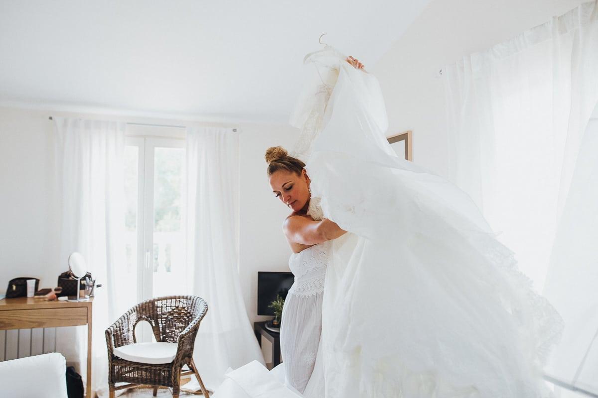 Die Braut nimmt Ihr Kleid vom Bügel um es an die frische Luft zu hängen.