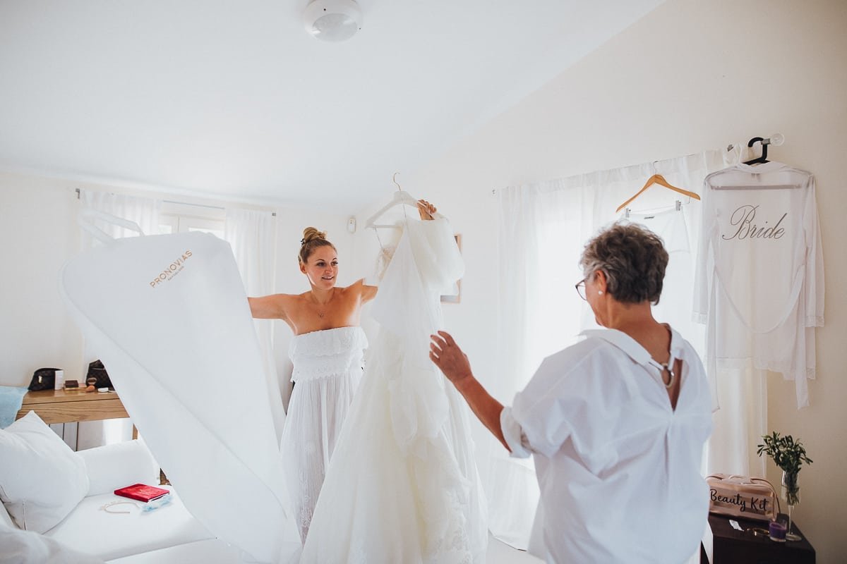 Die Braut und Ihre Mutter packen das Hochzeitskleid aus.