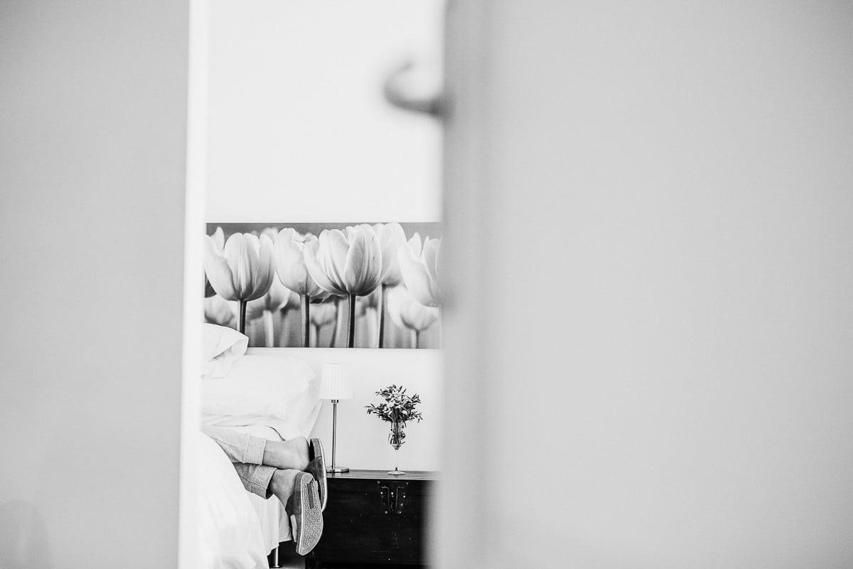 Kreativer Blickwinkel der Füsse des Bräutigams wie er auf dem Bett liegt in schwarz weiss.