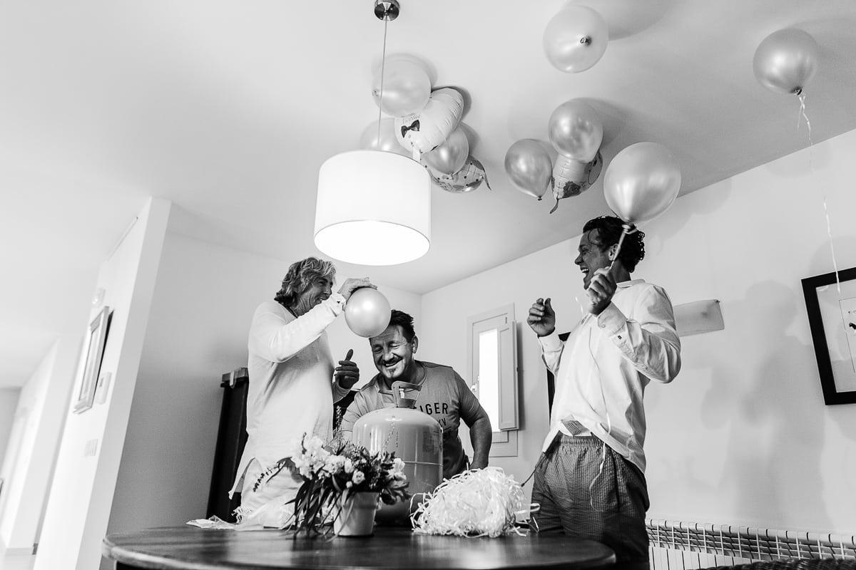 Die Männer der Familie blasen im Salon die Luftballons auf.