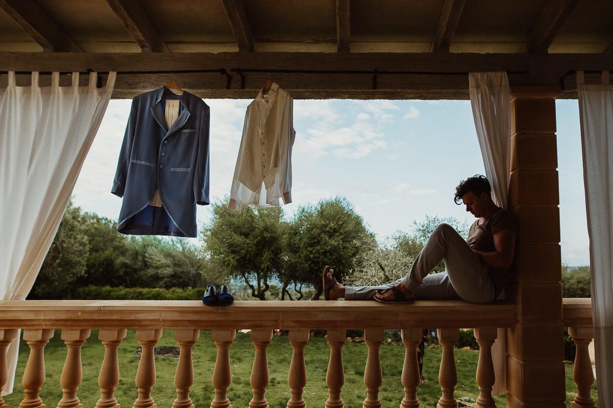Der Bräutigam sitzt gemütlich mit seinem Telefon auf der Brüstung der Veranda der Finca neben seinem Anzug der zum Lüften hängt.