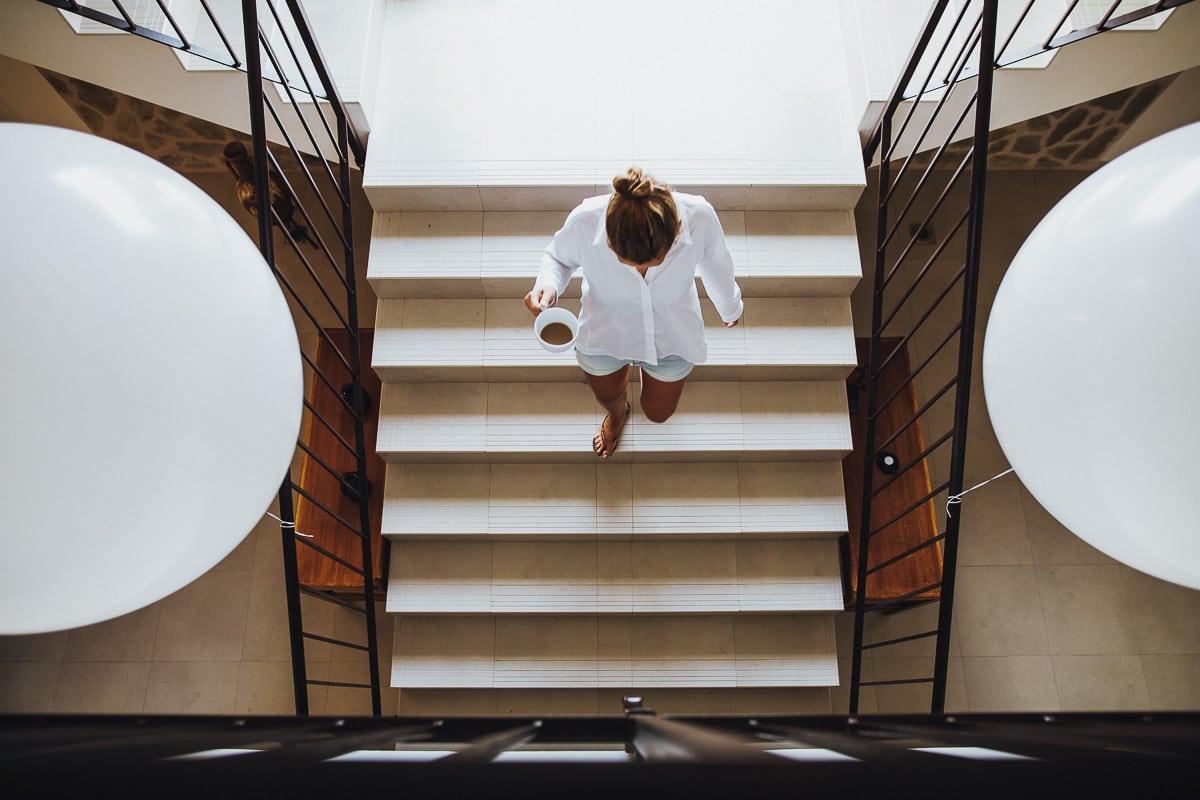 Eine der Gäste geht mit einer Tasse Kaffee zwischen den weissen Riesenballons die Treppe herunter.