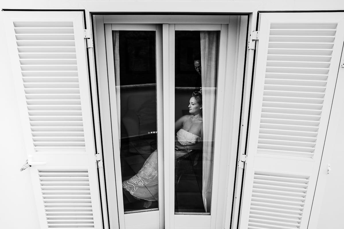 Die Braut während des Stylens von aussen durch das Fenster der Finca fotografiert.