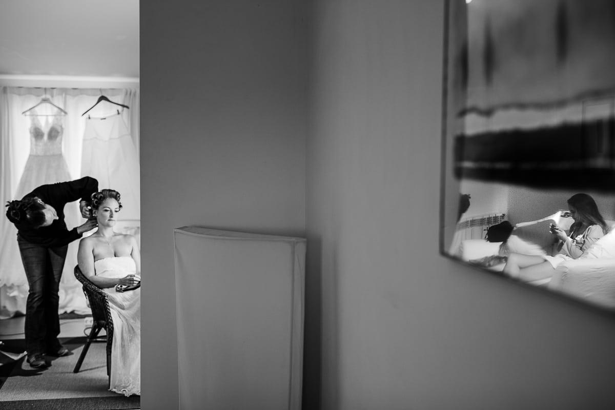 Die Braut bekomt Lockenwickler. In einem Wandbild spiegelt sich eine der Brautjungfern.