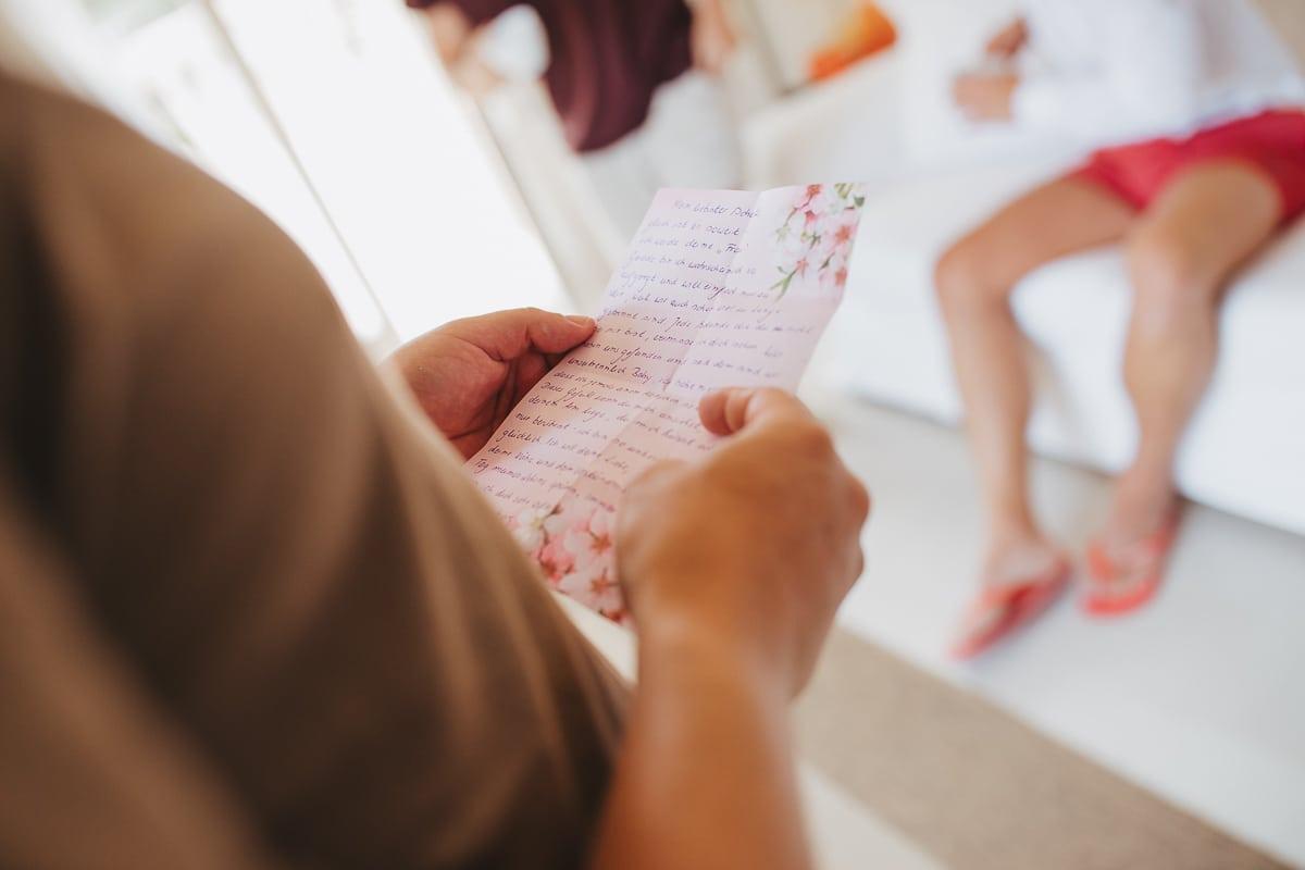 Der Bräutigam liesst den rosa Brief seiner Frau den er auf sein Zimmer getragen bekommen hat.