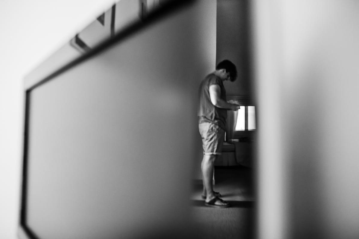 Der lesende bräutigam in einem effektvollen schwarz weiss Bild wo er sich im Fernsehr spiegelt.