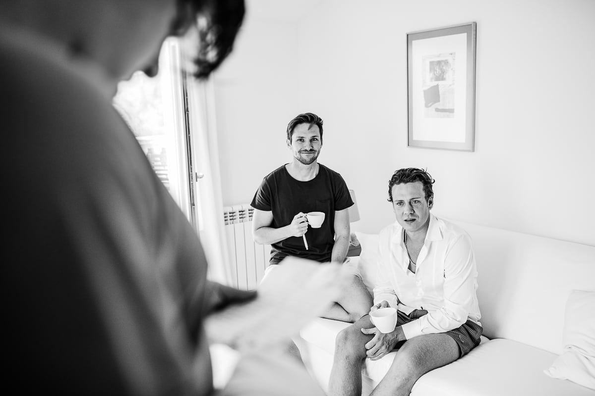 Der Bruder der Braut und der Bruder vom bräutigam sind bei ihm und sitzen auf dem Sofa während er den Brief seiner Zukünftigen liest.