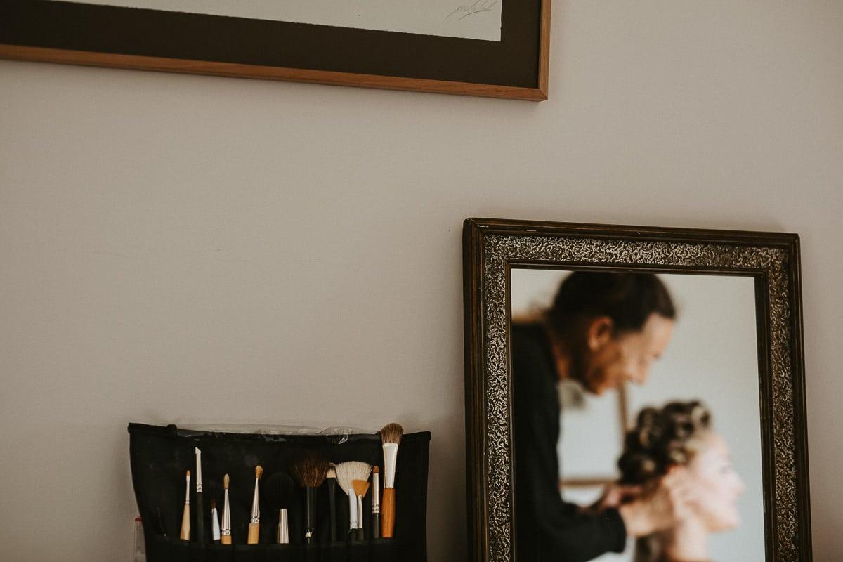Detailaufnahme der Schminkpinsel und Spiegelbild der Braut.