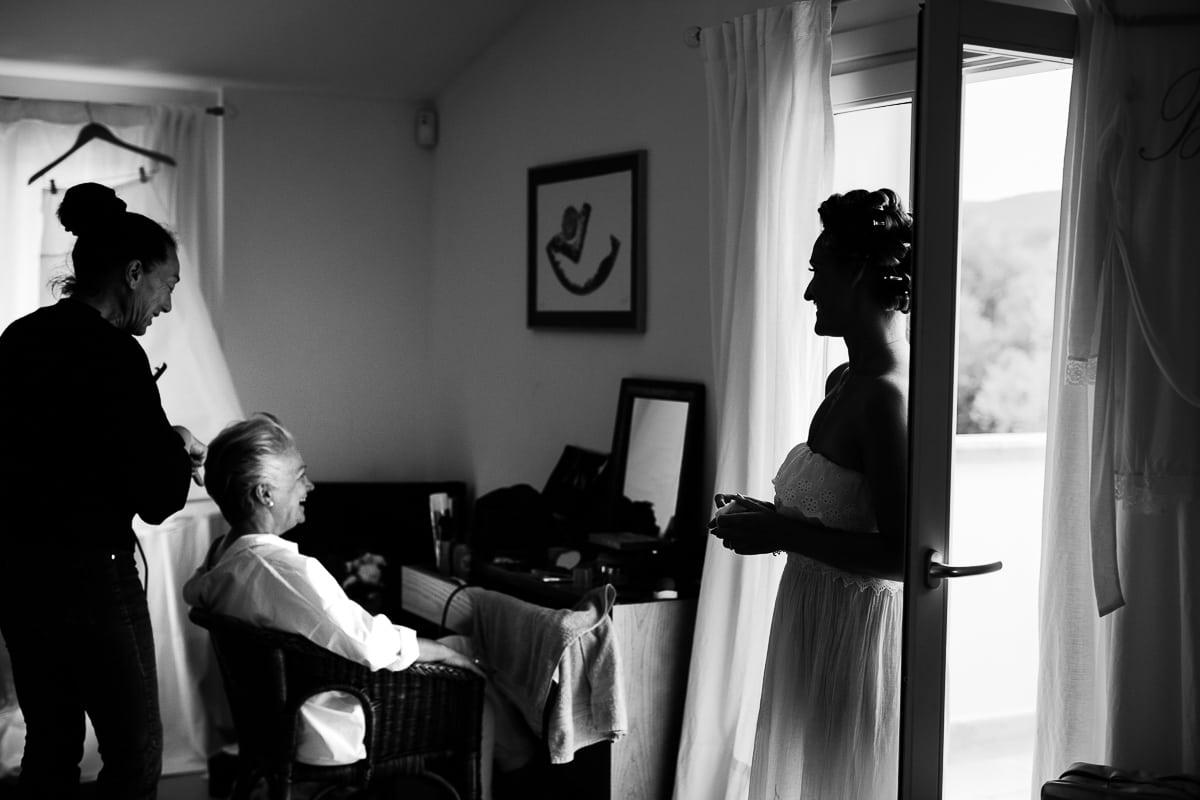 Die Brautmutter wird frisiert. die Braut steht am fenster und schaut zu.