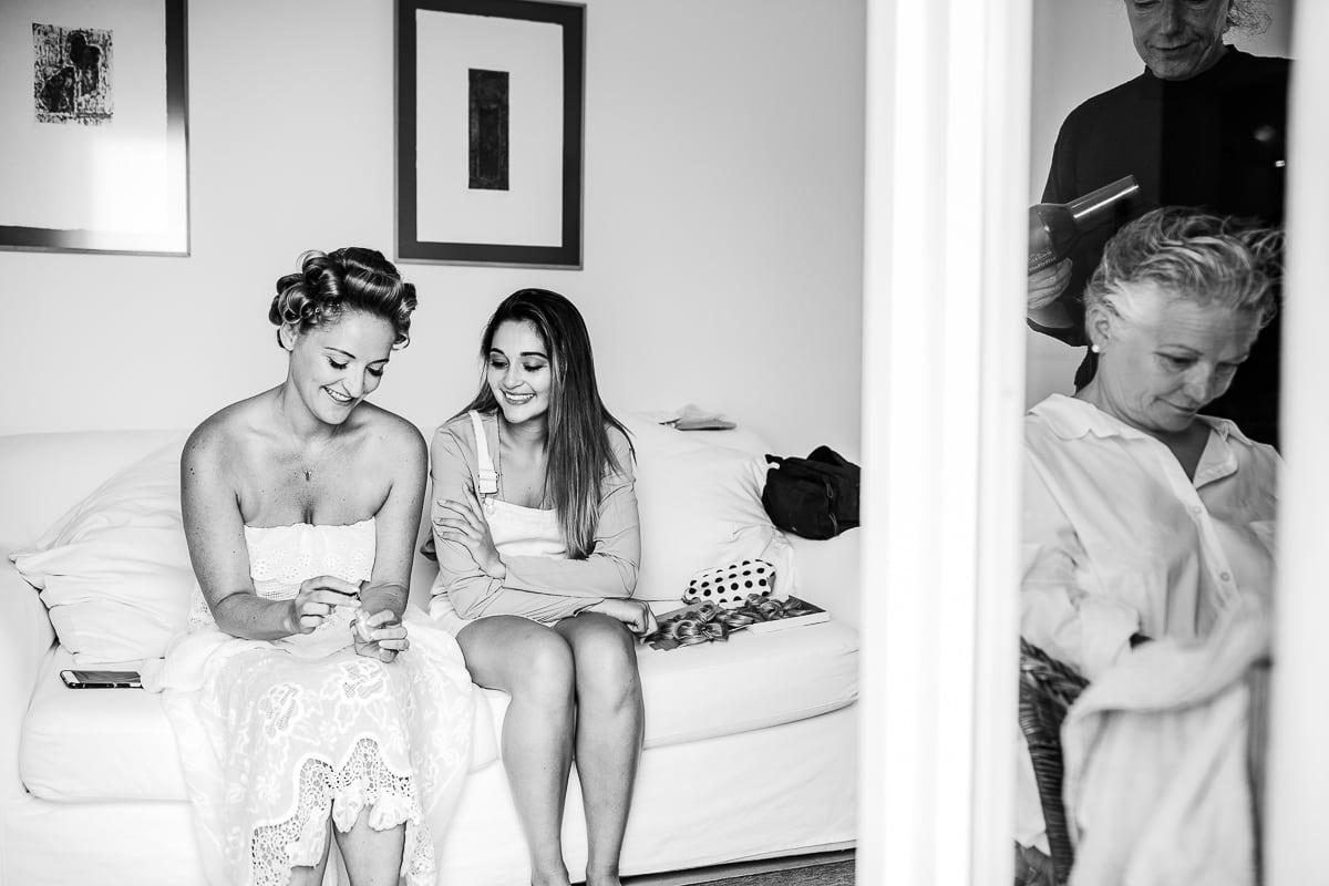 Während die Brautmutter zurecht gemacht wird sitzt die Braut lächelnd mit einer Brautjungfer auf dem Bett.