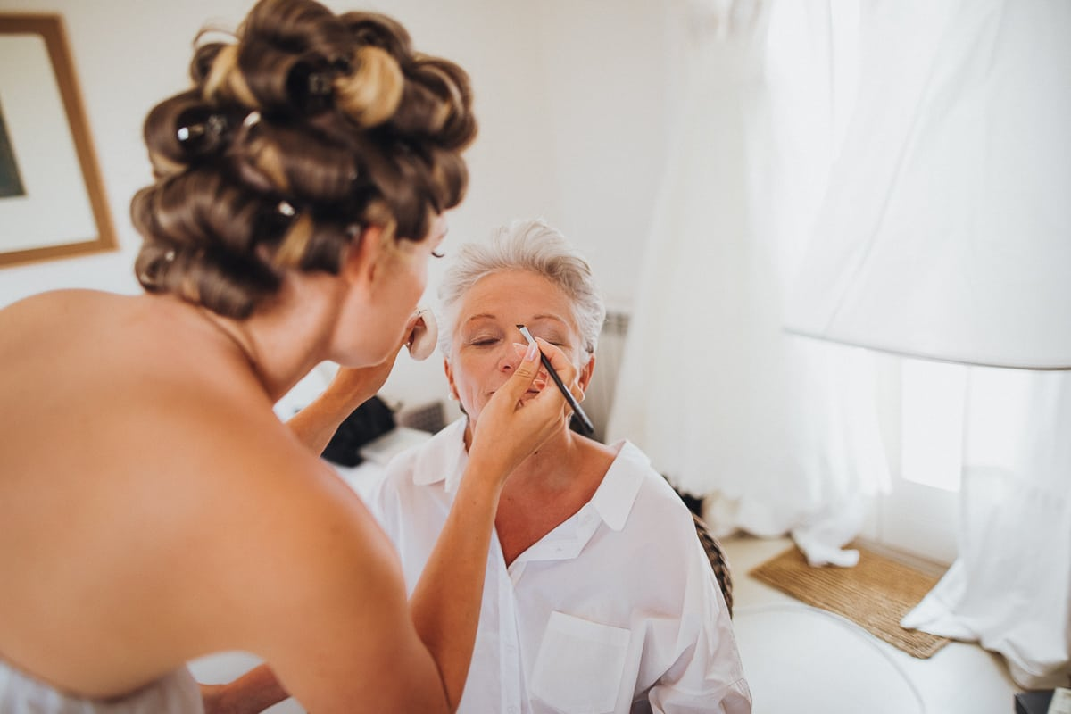 Nahaufnahme wie die Braut ihre Mutter selbst schminkt.