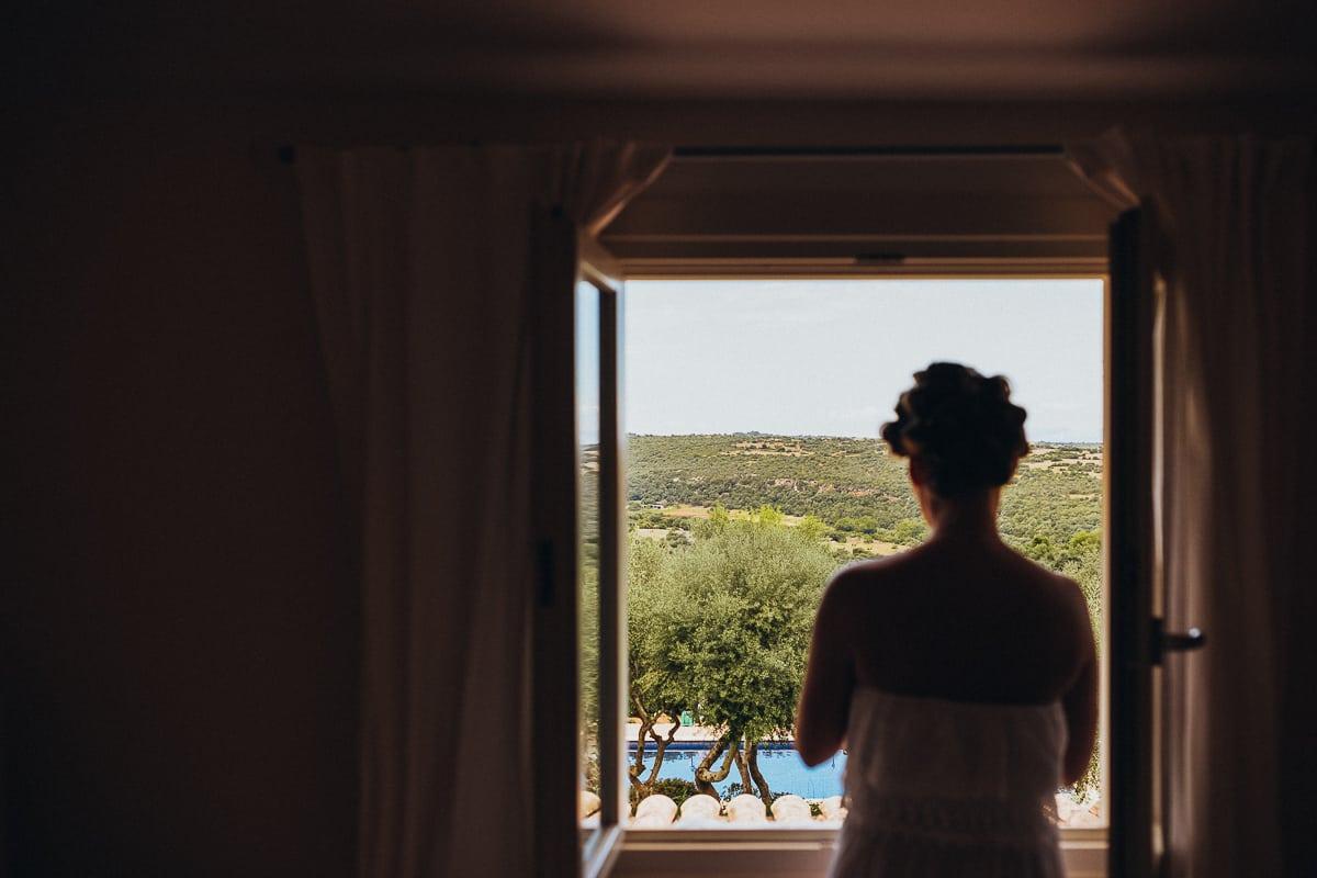 Die Braut steht am Fenster und schaut in die weite mallorquinische Landschaft.