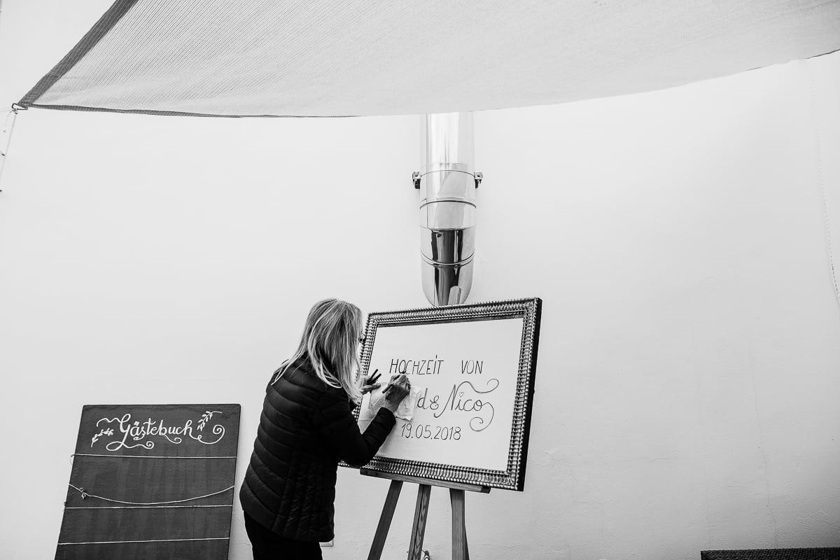 Momentaufnahme beim Bemalen des Willkommenschildes durch den Wedding Planer.