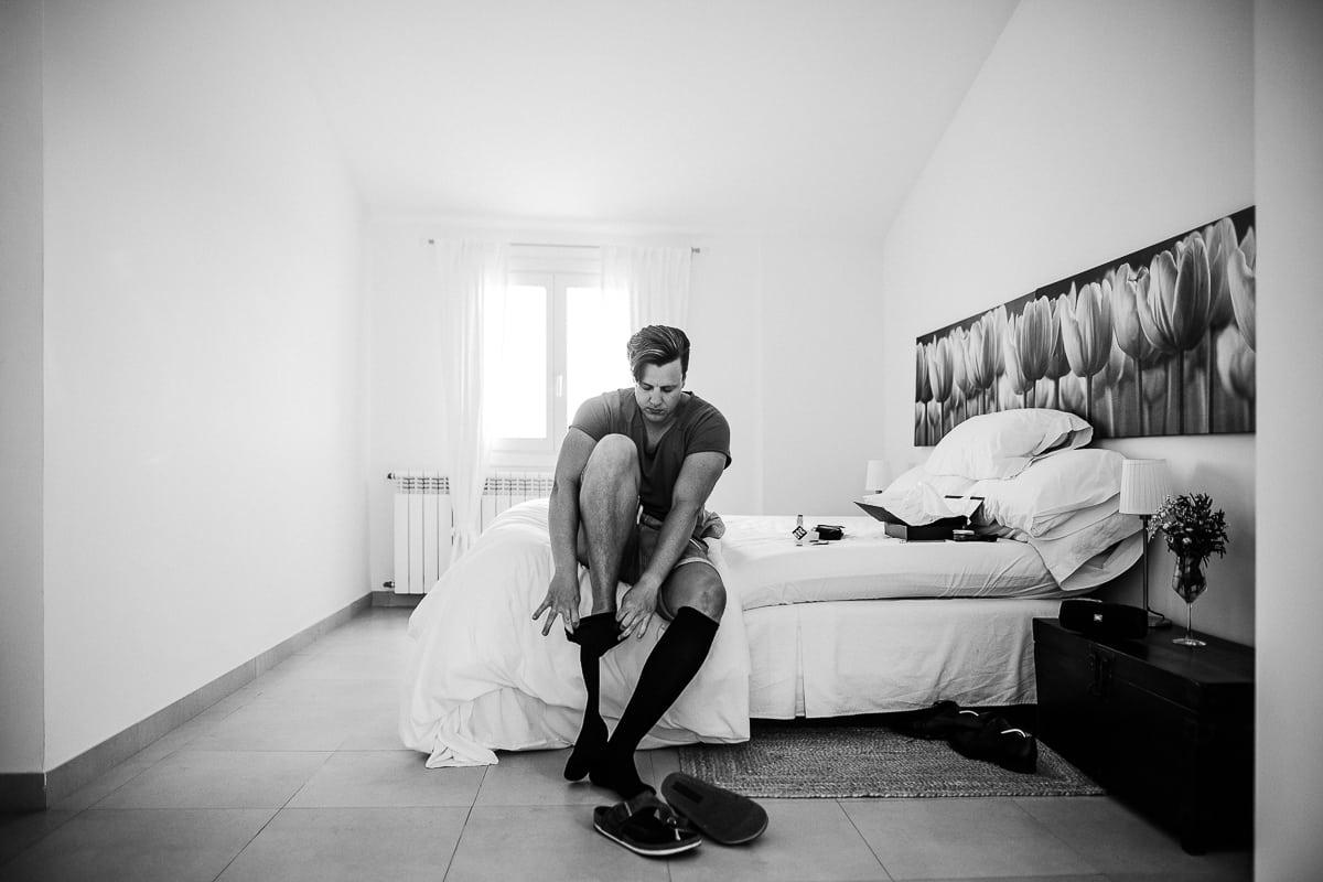 Der Bräutigam beginnt sich vorzubereiten und zieht seine Socken im Zimmer an.