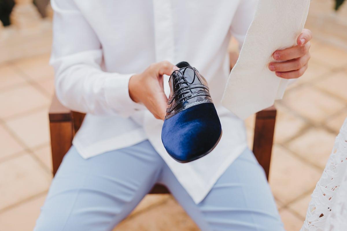 Der Bräutigam hält einen seiner Schuhe in der Hand um ihn anzuziehen.