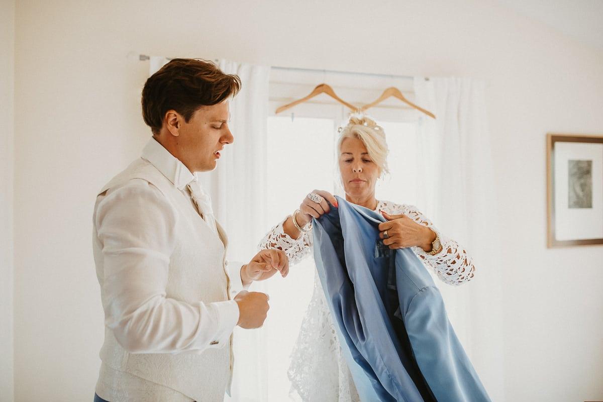 Die Mutter hilft ihren Sohn beim anziehen des Sakkos.
