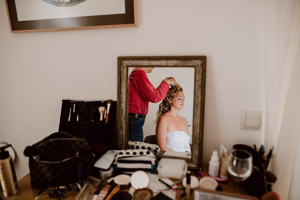 Die Braut mit geöffneten lockigen Haaren im Spiegel.