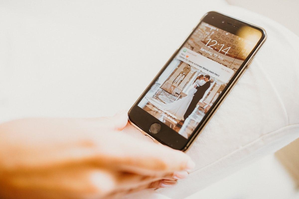 Detailsaufnahme vom Handy der Braut mit einer Liebesnachricht ihres Mannes.
