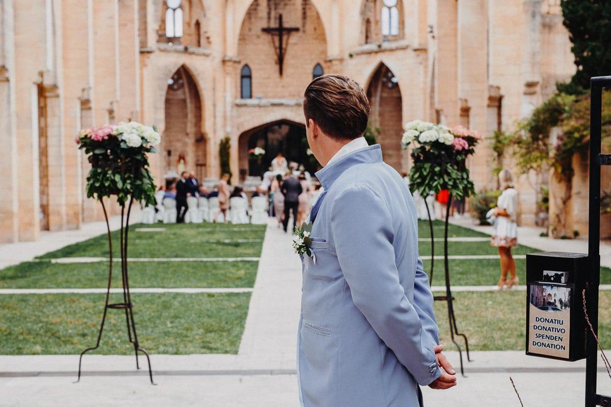 Der Bräutigam wartet am Eingang der Kirche.