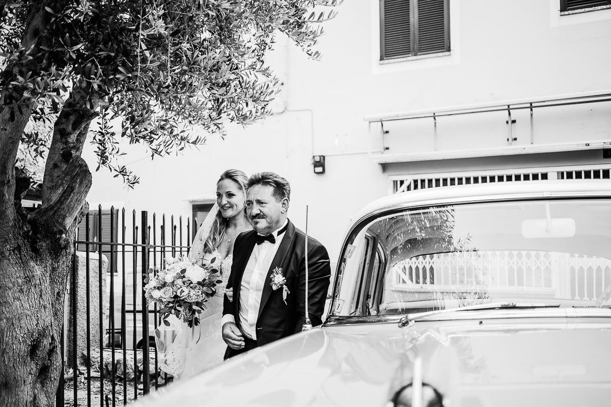 Der Vater und seine Tochter sind aus dem Oldtimer Hochzeitsauto ausgestiegen.